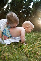 A boy kisses his baby brother´s back outdoors.