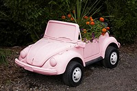 Pink decorative plastic miniature volkswagen Beetle planter with orange Zinnia and purple Petunia flowers in the Fairy garden in summer at the Route d...