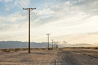 Drifting sand begins to cover roadway while power poles mark a border between desert and civilization.