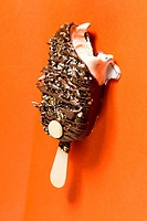 A chocolate bar isolotated on an orange background, drizled with toppings and more chocolate.