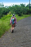 A young woman in a bathing suits walks alone on a road, Big Island, Hawaii