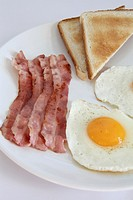 Breakfast with eggs, bacon and toasts.
