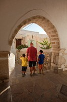 Man with the children at a passageway in the old town Chora, Naxos, Cyclades Islands, Greek Islands, Greece, Europe.