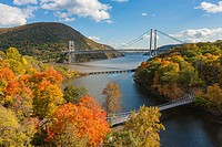 Autumn view of Bear Mountain Bridge in the distance with the CSX railroad bridge and the Popolopen Creek Suspension Footbridge in the foreground.
