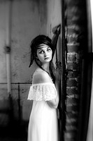 A 25 year old woman wearing a white dress looking at the camera standing in an abandoned building, black and white.