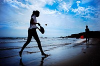 Boy and girl playing paddle beach tennis on the beach of Alcocebre, Castellon province, Valencian Community, Spain