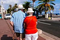 Elder couple walking on Promenade des Anglais. Nice, Alpes-Maritimes, French Riviera, Provence-Alpes-Côte d´Azur, France.