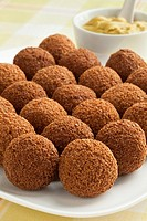 Dutch traditional snack bitterballen on a dish with mustard in the background.