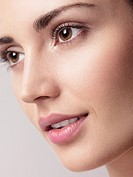 Closeup of a young beautiful woman face with brown eyes, clean natural look and smooth skin.