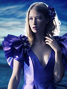 Beauty portrait of a young beautiful blond woman wearing a blue evening dress outdoors.