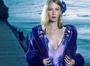 Beauty portrait of a young beautiful blond woman wearing a blue evening dress and a fur jacket outdoors at waterfront.