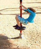 Boy with Blond Hair Spinning on a Pole at Playground.