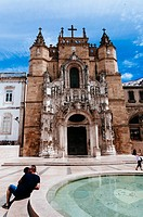 Tourists relaxing by a fountain in beautiful Praca 8 de Maio, May 8th square, with nice Santa Cruz church at back, Coimbra, Portugal.
