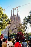 Tourists near la Sagrada Familia church designed by architect Antoni Gaudi. Barcelona, Catalonia, Spain