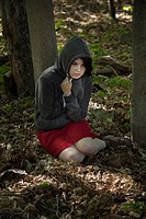Young woman, sitting on the ground in a park, wearing a sweatshirt and hoodie.