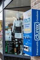 Rubber clad plastic mannequin next to Durex condom machine in town square pharmacy, Berques, France.