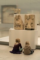 Two light haired children sat cross legged in front of two light stone crowned figure carvings, listening to historical commentaries, Louvre-Lens Muse...