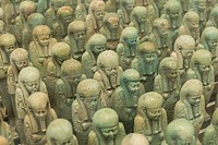 Many headed jade coloured funerary shabtis with stylised beads and symbolic regalia, Louvre-Lens Museum. Lens, France.