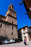 Old woman walking by village church, Rubielos de Mora, Teruel, Spain.