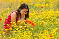 Girl with a red dress picking up flowers in a yellow field.