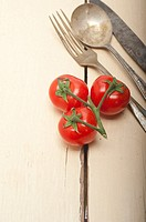 ripe cherry tomatoes cluster over white rustic wood table.