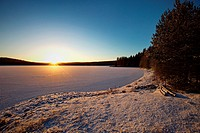 An ice covered lake in northern Sweden is illuminated by the low winter sun. Agnsjön, Bredbyn, Västernorrland, Sweden.