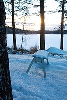 Wooden bench standing at the shore of an ice covered lake. Agnsjön, Bredbyn, Västernorrland, Sweden.