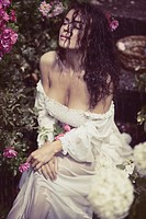 Romantic sensual portrait of a beautiful sexy young woman with wet dark hair and wet summer dress sitting alone in the rain in a rose garden.