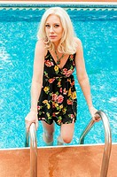 A 31 year old blond woman looking at the camera in a summer dress next to on the steps of a swimming pool ladder.