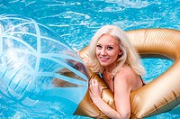 A smiling 31 year old blond woman playing on an inflatable toy in a swimming pool.