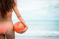 Woman beach fitness - back side of attractive female holding beach volleyball, Riviera Nayarit, Mexico.
