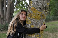 young girl embracing the trunk of an ash tree, France, Europe.