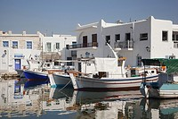 Whitewashed houses with colorful doors and windows in town center with the traditional fishing boats in the foreground, Naoussa, Paros, Cyclades Islan...
