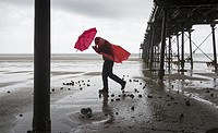 A man walking under Saltburn`s Victorian pier during a torrential summer downpour at Saltburn by the sea, North Yorkshire, England, United Kingdom.