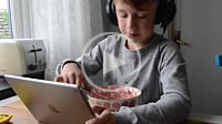 Boy 9 years old eat and looks at tablet-pc
