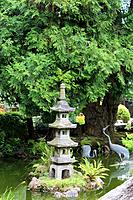A landscaped Japanese garden with a Japanese stone lantern and bird statues in a pond in California, USA.