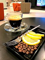 Cup of carajillo, coffee and brandy, with coffee beans and sliced lemon in a cafe.