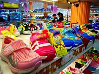 Colourful childrens infants plastic shoes trainers on display in shoe store shop in the Chinese city of Taiyuan, Shandong province, China.