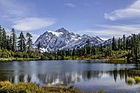 WASHINGTON - Mount Shuksan reflecting in Picture Lake in Heather Meadows Recreation Area in the North Cascades. Fall colours are abundant in the veget...