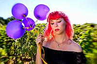 A 25 year old woman with pink hair, looking down in a field of sunflowers holding balloons, Alabama USA.