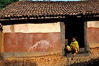 Woman belonging to the Kutia Kondh tribe seating in front of her house ( Odisha state, India).