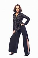Young dark-haired girl in stylish clothes posing in front of camera. The girl is very cute and has a model appearance and a good slender figure. Cloth...