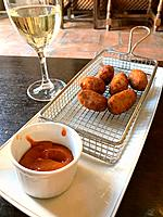 Croquettes with tomato sauce and glass of white wine. Spain.