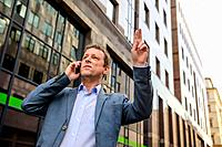 A middle age businessman standing and waving for a taxi while speaking on the phone.