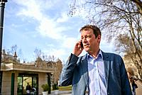 A middle age businessman standing in a park while talking on his phone.