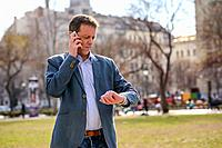 A middle age businessman standing in a park while talking on his phone and checking the time on his watch.