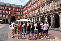 Tourists enjoying a guided tour in the Plaza Mayor, Madrid, Spain