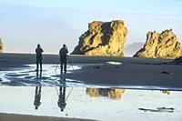Photographers and Sea stack rocks at Bandon Beach at low tide, Bandon, Oregon, USA.