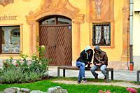 men on a park bench, Mittenwald, Bavaria, Germany.
