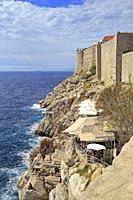 Restaurants on the rocks below Dubrovnik Old City walls, Croatia, UNESCO world heritage site, Dalmatia, Dalmatian Coast, Europe.